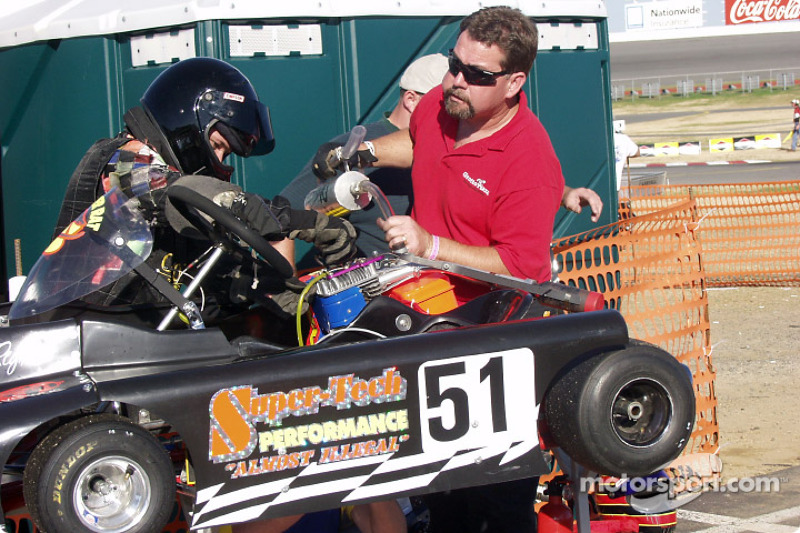 Crewmember Terry Jester fuels the #51 machine and watches driver Jace Reynolds makes final adjustments to their new engine