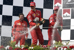 The podium: champagne for race winner Rubens Barrichello, Michael Schumacher and Jean Todt