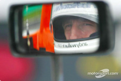 Andy Wallace peers into the rearview mirror of the #16 Judd-engined Crawford, fielded by Dyson Racing Team, while sitting on the grid at the VIR 500