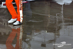 Brett Bodine splashes his way to the garage area during a rain delay