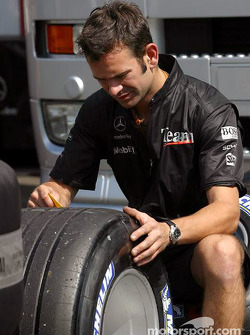 McLaren team member prepares the tires