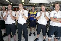 Jaguar team members watch Mark Webber's qualifying lap