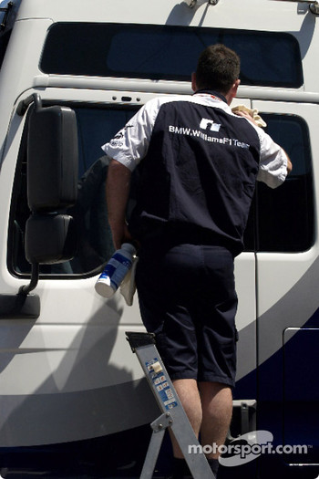 Williams-BMW team member washes the transporter