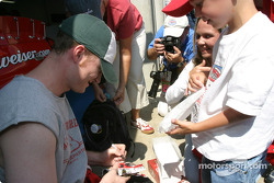 Dale Earnhardt Jr. signs his autograph on a #8 diecast car