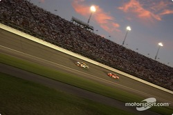 Elliott Sadler and Robby Gordon fight for position as the lights come up