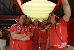 Ferrari team members watch Michael Schumacher qualifies