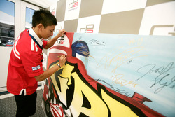 Rio Haryanto signing some art work