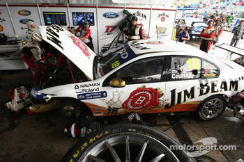 Team mechanics work on the car of James Courtney, #18 Jim Beam Racing