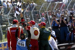 Race winner Sébastien Bourdais celebrates with Justin Wilson and Alex Tagliani