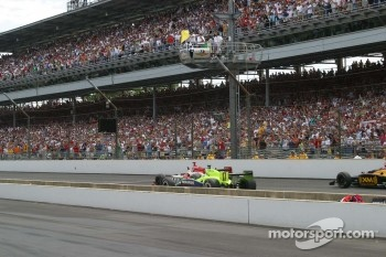 Dan Wheldon wins the race with checkered and yellow flags.