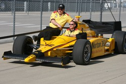Members of the #12 Symantec Luczo Dragon Racing team return driver Ryan Briscoe's car to the garage area