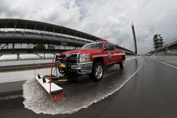 Track workers dry pit lane after an afternoon shower at the Indianapolis Motor Speedway during bump day.