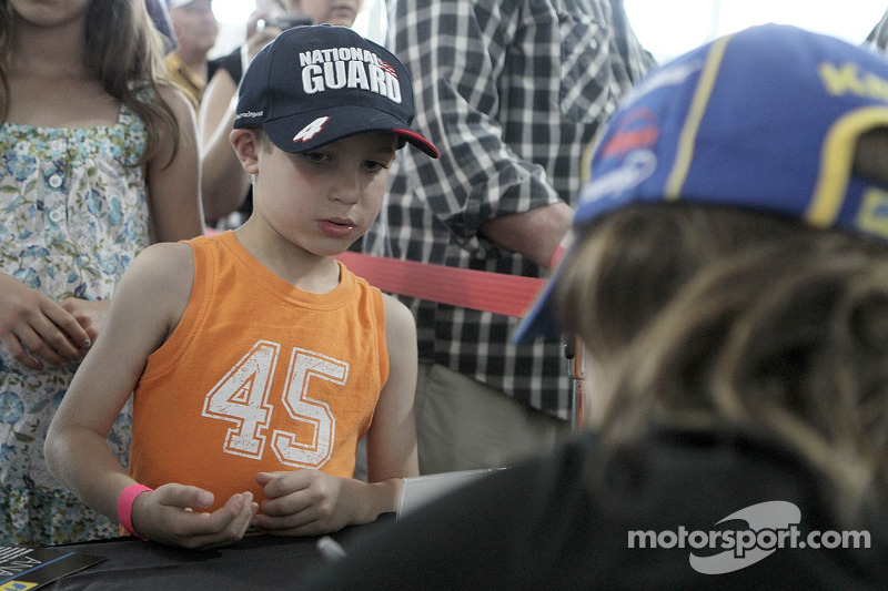 A young fan gets an autograph from Ana Beatriz