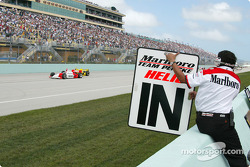 Helio Castroneves getting his position by a Penske crew member