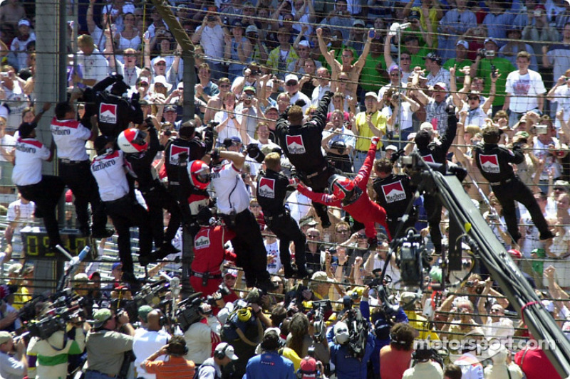 Castroneves and the entire crew celebrate by climbing the fence