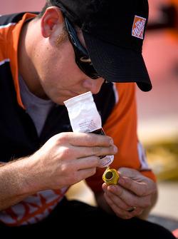 Joe Gibbs Racing Toyota team member prepares wheels