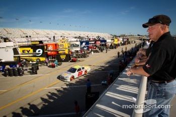 Fans watch garage activity as A.J. Allmendinger, Penske Racing Dodge drives by