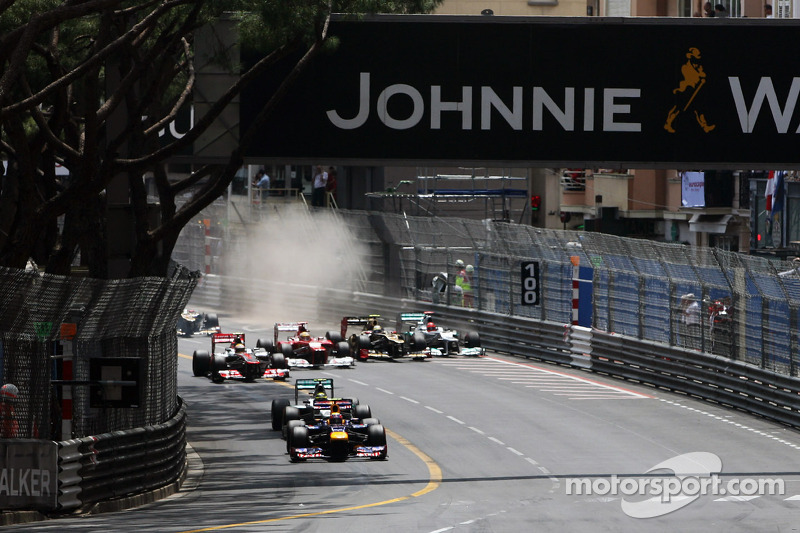Mark Webber, Red Bull Racing leads at the start of the race as Michael Schumacher, Mercedes AMG F1 and Romain Grosjean, Lotus F1 make contact