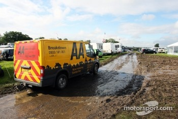 Wet and muddy car parks and camp sites at the circuit with an AA van