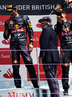 Sebastian Vettel, Red Bull Racing pours champagne on Jackie Stewart, on the podium as race winner Mark Webber, Red Bull Racing talks to the crowd