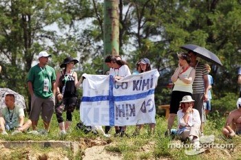 Fans on the grassy banks with a finnish flag for Kimi Raikkonen, Lotus F1 Team