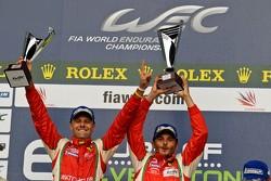 Gianmaria Bruni and Giancarlo Fisichella proudly raise their trophies