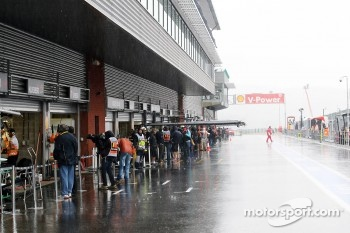 Heavy rain falls in the pit lane