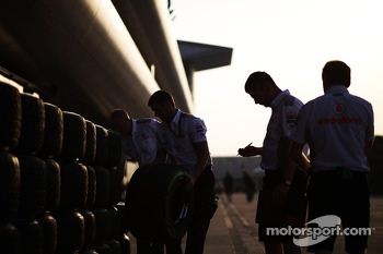 McLaren mechanics with Pirelli tyres as the sun sets over the paddock