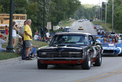 Race cars parade into Elkhart Lake for the Friday concours.