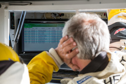 Corvette pit crew member watching timing and scoring during qualifying