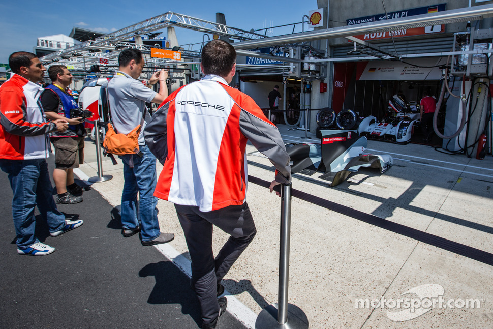 Porsche team members watch the repairs on the #1 Audi Sport Team Joest Audi R18 E-Tron Quattro