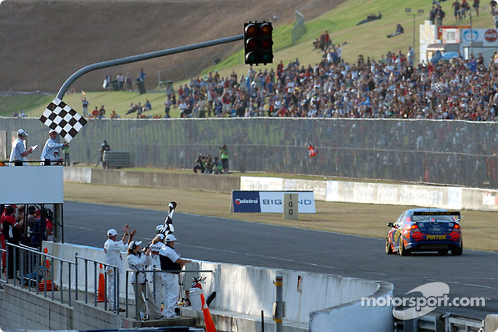 Marcos Ambrose takes the chequered flag and seals the 2004 V8 Supercar Championship
