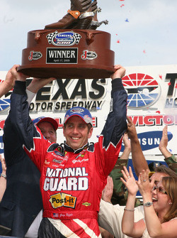Victory lane: race winner Greg Biffle hoist the Justin Boot Trophy