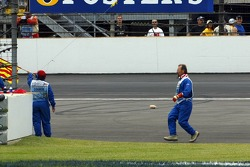 A marshall goes to recover bottles and cans of beer thrown on the track