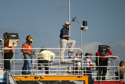 Crew members monitor on-track action from atop team haulers