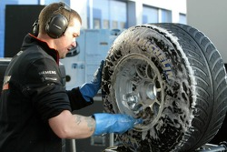 McLaren team member washes tires