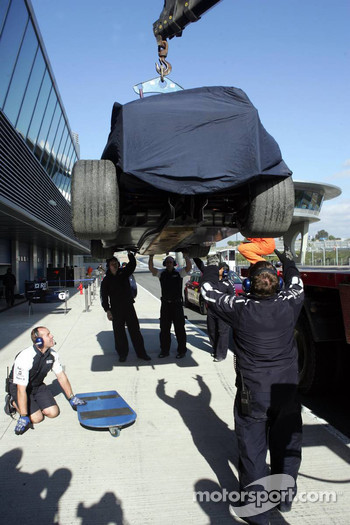 Car of Mark Webber returns to the pits after stopping on the track