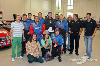 The Red Hot Chili Peppers poses with a pit crew in the garage of Rousch Racing