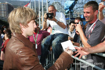 Nick Heidfeld signs autographs for fan with Michel Comte in the background