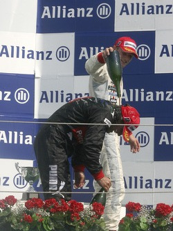 Giorgio Pantano celebrates victory on the podium with Alexandre Premat