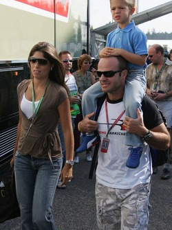 Rubens Barrichello arrives with a kid on his shoulders
