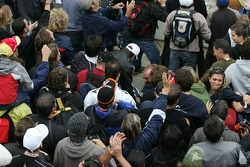 Fans fight for the hats thrown away by the drivers