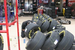 Crew members work on tires before the race