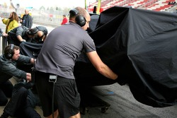 The car of Lewis Hamilton is returned to the pits after a problem with his wheel on track
