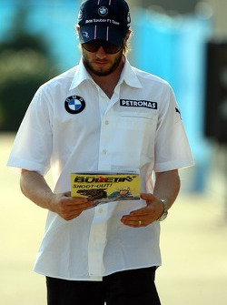 Nick Heidfeld, BMW Sauber F1 Team arrives at the track and reads THE RED BULLETIN