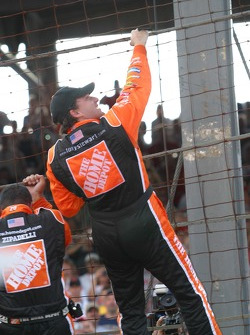 Race winner Tony Stewart climbs the fence