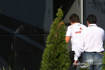 Fernando Alonso and his manager Luis Garcia Abad enter the bus of Bernie Ecclestone