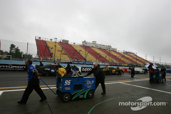 Crew members push cars back to the garage area as the qualifying session is cancelled