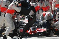 Lewis Hamilton, McLaren Mercedes and a mechanic with his blown tyre