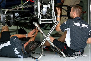 Red Bull Racing team members work on their car